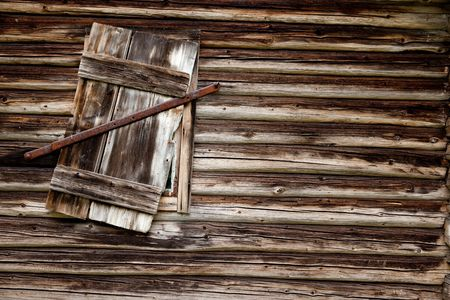 A weathered log cabin background texture with old window photo