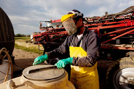 pesticides: Filling a high clearance sprayer with chemical and water with proper safety equipment