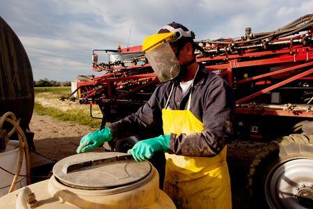 pulverizador: Rellenar un rociador de holgura alta con químicos y agua con equipo de seguridad adecuado