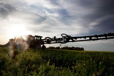 chemical fertilizer: A silhouette of a high clearance sprayer on a field with solar flare. Stock Photo