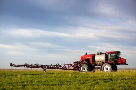 pesticides: A high clearance sprayer on a field  in a prairie landscape
