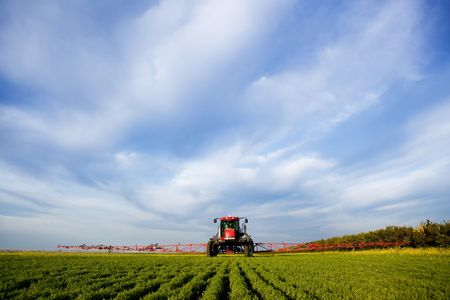 A high clearance sprayer on a field  in a prairie landscape photo