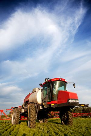 chemical fertilizer: A high clearance sprayer on a field  in a prairie landscape