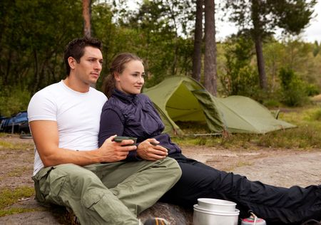 A couple sitting enjoying eachothers company while camping photo