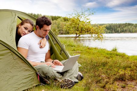 A couple looking at a computer while camping in a tent photo