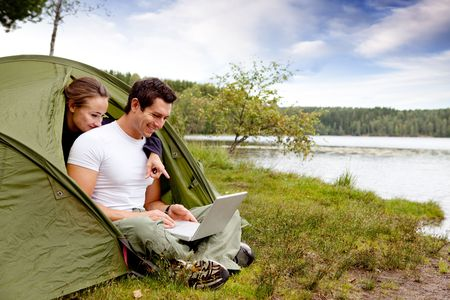 laptop outside: A couple looking at a computer while camping in a tent Stock Photo