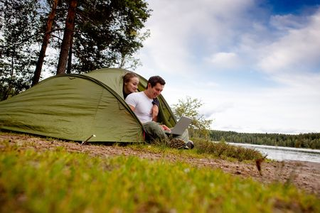A man and woman using a computer outdoors in a tent Stock Photo - 5812531