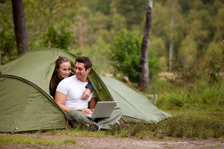 A couple using a computer outside a tent on a camping trip photo