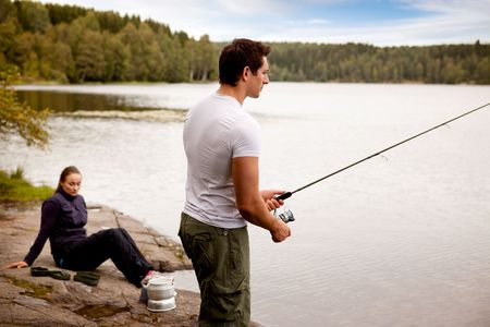 A man fishing on a lake with camping equipment and woman in background photo