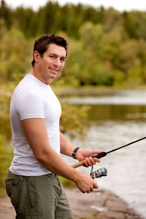 A man fishing on a inerior lake with forest in the background Stock Photo - 5812517