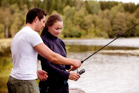 A man showing a woman how to fish photo