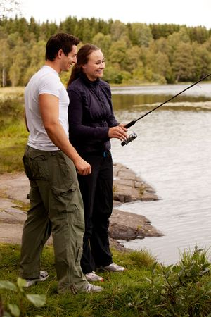 A young adult couple having fun fishing on a forest lake. photo