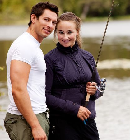 A happy camping couple in the forest fishing photo