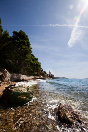 The coast of croatia on the Island of Rab with the old city in the background photo
