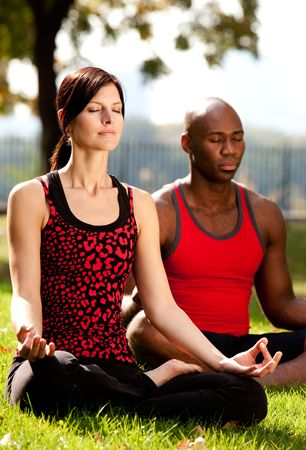 Two people meditating in a city park on a sunny day photo
