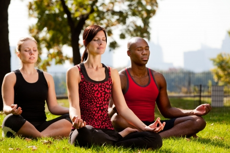 A group of people doing yoga in a city park photo
