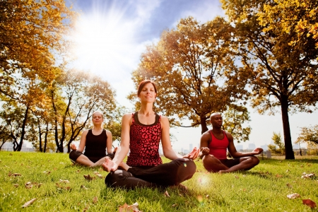 A group of people meditation in a city park in the morning - taken into the sun with lens flare photo