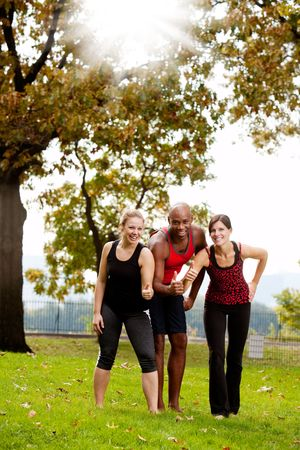 A group of friends exercising in the park - giving the thumbs up  photo