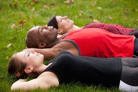 A group of people relaxing in a park after exercise photo