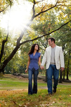 A happy couple walking in the park - looking at each other photo