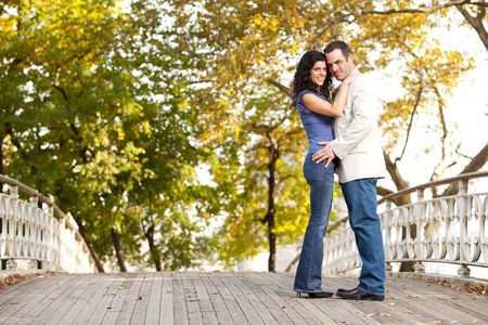 A happy couple in the park looking at the camera and hugging Stock Photo - 5897942