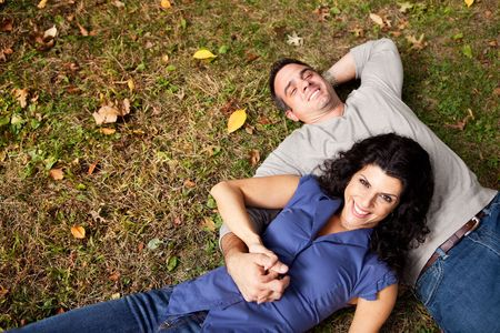 A happy couple daydreaming in a park on grass - sharp focus on woman photo