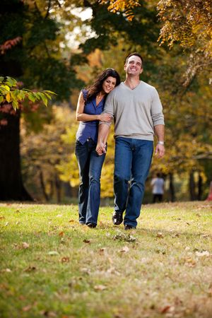 A happy couple walking in the park on grass photo