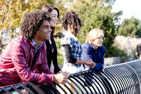 A group of friends outside in a park having fun - shallow depth of field with sharp focus on first person photo
