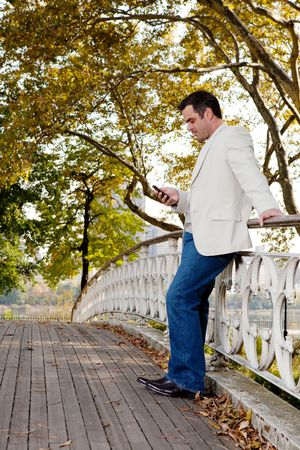 A man checking his cell phone in a park photo
