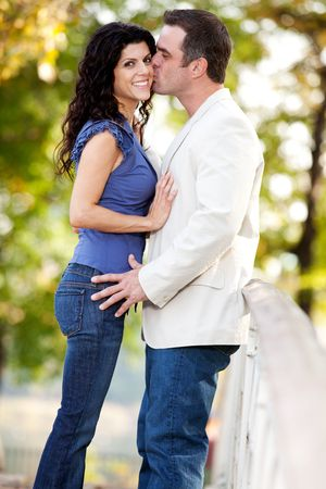 A man kissing a woman on the cheek in a park Stock Photo - 5971848