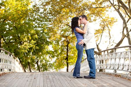 A couple kissing while walking in the park Stock Photo - 5971854