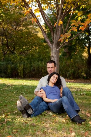 A couple relaxing in the park by a tree photo