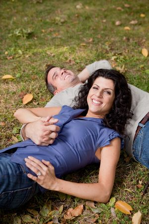 A happy couple relxing laying in the grass - sharp focus on the woman photo