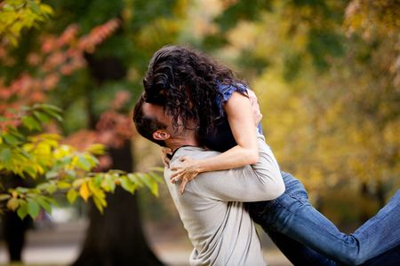 engaged: A man giving a woman a big hug in a park Stock Photo