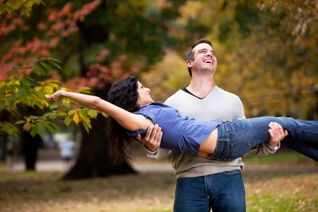 A playful couple - man holding woman in the park photo