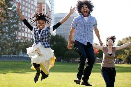 euphoric: Un gruppo di persone saltando di gioia in un parco urbano Archivio Fotografico
