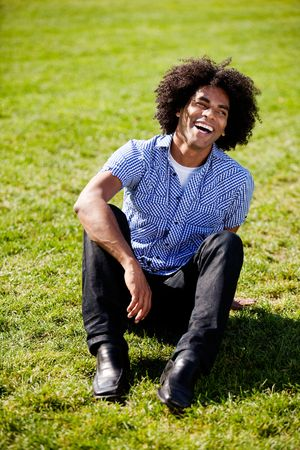 An African American sitting on grass with a natural laugh Stock Photo - 5981935
