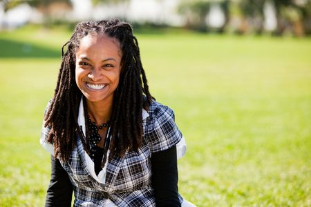A beautiful African American woman isolated on grass photo