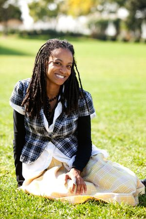 A young African American student sitting on grass Stock Photo - 5981927