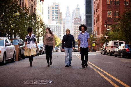 A group of young adults in an uban setting - walking on a road photo