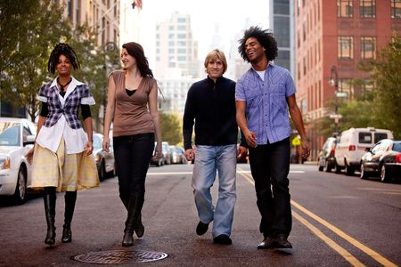 A group of young people walking down a street in a large city photo