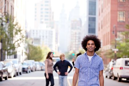 A city setting with a group of friends, a happy African American in the foreground photo