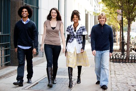 A group of friends walking on the sidewalk in an urban setting photo