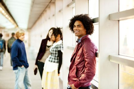 hang out: An African American male with friends talking in the background