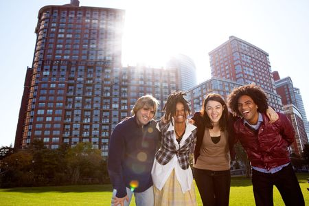 friend hug: A group of young adults in a city park - shot into the sun with solar flare Stock Photo