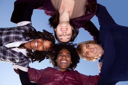 multicultureel: Een groep van vrienden in een cirkel te knuffelen en kijken naar de camera