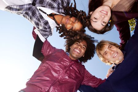 young boy smiling: A group of friends hugging and looking down on the camera