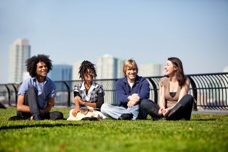 A group of friends in a city park talking and laughing photo