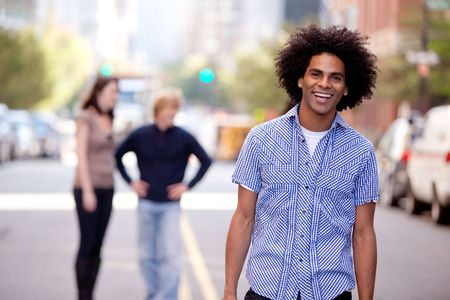 A happy young adult in a city setting with friends Stock Photo - 6053460