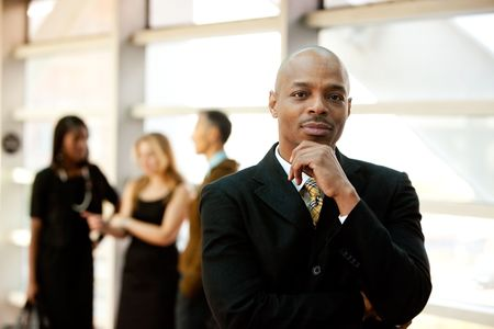 african business: An African American business man with co-workers in the background Stock Photo